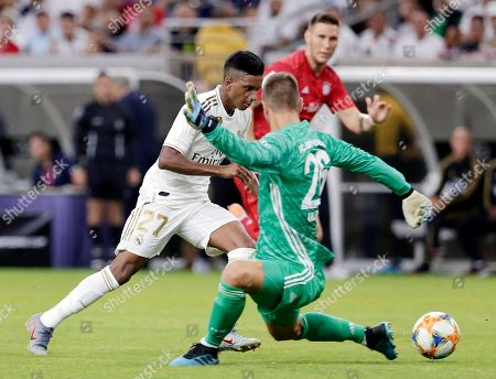 Real Madrid forward Rodrygo Goes (27) is tripped by FC Bayern goalkeeper Sven Ulreich (26) as he tries to score while Niklas Süle, looks on during the second half of an International Champions Cup soccer match, in Houston. Ulreich received a red card for a professional foul on the play