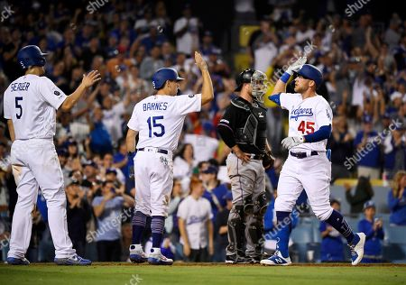 Matt Beaty, Austin Barnes, Bryan Holaday. Los Angeles Dodgers' Matt Beaty, right, is congratulated by Corey Seager, left, and Austin Barnes, second from left, as Miami Marlins catcher Bryan Holaday stands at the plate during the eighth inning of a baseball game, in Los Angeles