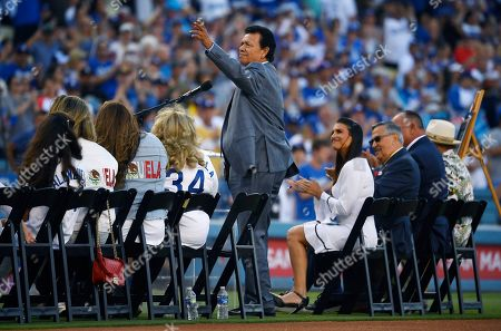 """Former Los Angeles Dodgers pitcher Fernando Valenzuela waves to fans as he is inducted into the """"Legends of Dodger Baseball"""" prior to a baseball game against the Miami Marlins, in Los Angeles"""