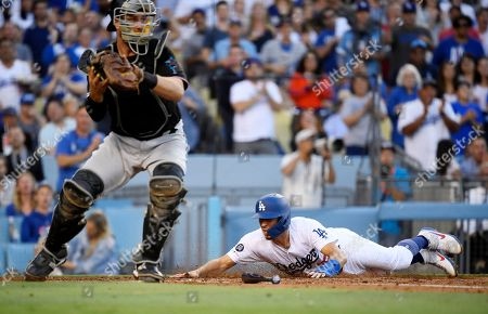 Austin Barnes, Bryan Holaday. Los Angeles Dodgers' Austin Barnes, right, scores on a single by Clayton Kershaw as Miami Marlins catcher Bryan Holaday gets set to throw out Kershaw at second during the fourth inning of a baseball game, in Los Angeles