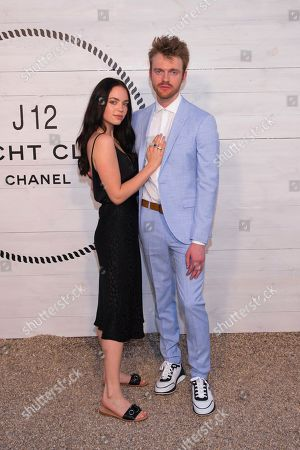 Stock Picture of Claudia Sulewski, Finneas O'Connell. Claudia Sulewski, left, and Finneas O'Connell attend Chanel's J12 Yacht Club dinner event at Sunset Beach, in Shelter Island, NY