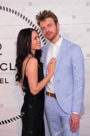 Stock Image of Claudia Sulewski, Finneas O'Connell. Claudia Sulewski, left, and Finneas O'Connell attend Chanel's J12 Yacht Club dinner event at Sunset Beach, in Shelter Island, NY
