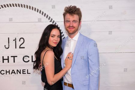 Stock Photo of Claudia Sulewski, Finneas O'Connell. Claudia Sulewski, left, and Finneas O'Connell attend Chanel's J12 Yacht Club dinner event at Sunset Beach, in Shelter Island, NY