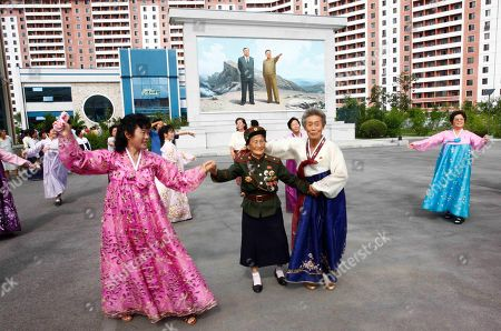 Stock Picture of A war veteran, center, dances with people in front of images of their late leaders, Kim Il Sung, left, and Kim Jong Il, outside Pyongyang Bag Factory turned into a polling station in Pyongyang, North Korea, . North Korea is holding local elections across the country Sunday, in a routine that normally happens once every four years. The voting is usually surrounded by organized singing and dancing at polling stations, an official celebration of the vote