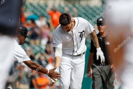 Detroit Tigers third base coach Dave Clark reaches out to designated hitter Nicholas Castellanos as he rounds third on a walk off solo home run during the tenth inning of a baseball game against the Toronto Blue Jays, in Detroit
