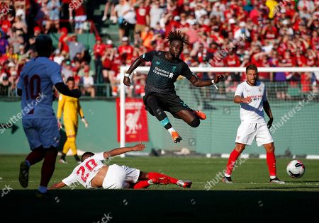 Liverpool's Divock Origi, center, leaps over Sevilla's Diego Carlos Santos Silva (20) during the first half of a friendly soccer match at Fenway Park, in Boston
