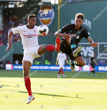 Stock Picture of Sevilla FC Diego Carlos Santos Silva (L) and Liverpool FC Alex Oxlade-Chamberlain (R) battle for the ball during the first half  of their friendly match held at Fenway Park in Boston, Massachusetts, USA, 21 July 2019.