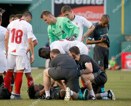 Sevilla's Joris Gnagnon (24) leans down to shake hands with injured player Liverpool's Yasser Larouci as Liverpool goalkeeper Simon Mignolet (22) and Sevilla's Escudero (18) look on during the second half of a friendly soccer match at Fenway Park, in Boston