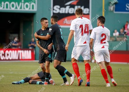 Liverpool's Ki Jana Hoever, center, restrains Adam Lewis as Sevilla's Maximillian Wober (14) blocks Sebastien Mathieu Corchia (2) as they argue after an injury to Liverpool's Yasser Larouci, laying on turf, during the second half of a friendly soccer match at Fenway Park, in Boston