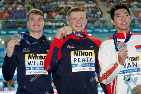 Gold medalist Britain's Adam Peaty, centre, holds up his medal with silver medalist and compatriot James Wilby, left, and bronze medalist Chian's Yan Zibei following the men's 100m breaststroke final at the World Swimming Championships in Gwangju, South Korea