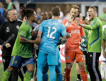 Seattle Sounders goalkeeper Stefan Frei, second from right, reacts as Portland Timbers goalkeeper Steve Clark (12) and Sounders defender Roman Torres, second from left, exchange words after an MLS soccer match, in Seattle. The Timbers won 2-1
