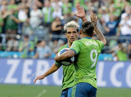 Seattle Sounders forward Raul Ruidiaz, right, is greeted by forward Nicolas Lodeiro, left, after Ruidiaz scored a goal against the Portland Timbers during the second half of an MLS soccer match, in Seattle. The Timbers won 2-1