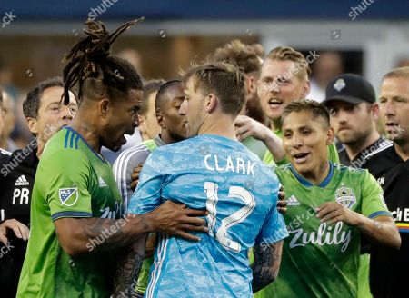 Seattle Sounders defender Roman Torres, left, has works with Portland Timbers goalkeeper Steve Clark (12) as Sounders' Raul Ruidiaz, right, looks, after an MLS soccer match, in Seattle. The Timbers won 2-1