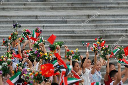 Children wave flowers and flags during a welcome ceremony for Abu Dhabi's Crown Prince Sheikh Mohammed bin Zayed Al Nahyan at the Great Hall of the People in Beijing