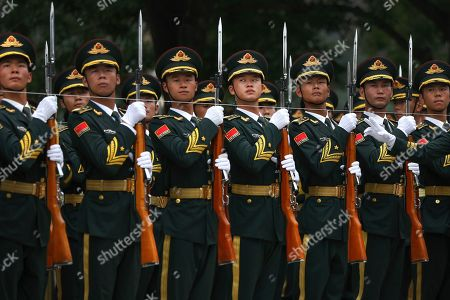 Members of an honor guard prepare for a welcome ceremony for visiting Abu Dhabi's Crown Prince Sheikh Mohammed bin Zayed Al Nahyan at the Great Hall of the People in Beijing