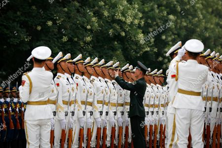 A Chinese People's Liberation Army soldier adjusts a hat of an honor guard member as they prepare for a welcome ceremony for visiting Abu Dhabi's Crown Prince Sheikh Mohammed bin Zayed Al Nahyan at the Great Hall of the People in Beijing