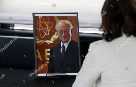 An employee signs a book of condolence in front a photo of Director General of the International Atomic Energy Agency, IAEA, Yukiya Amano from Japan in Vienna, Austria, . The IAEA announced the death of the agency's Director General Yukiya Amano at the age of 72 years