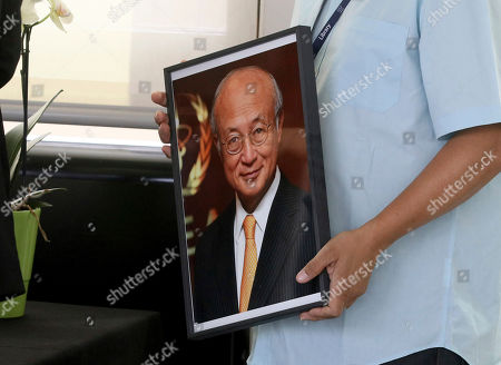 An employee holds a portrait photo of the Director General of the International Atomic Energy Agency, IAEA, Yukiya Amano from Japan in Vienna, Austria, . The IAEA announced the death of the agency's Director General Yukiya Amano at the age of 72 years