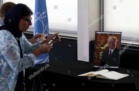 People take a pictures of the condolence book and a portrait photo of Director General of the International Atomic Energy Agency, IAEA, Yukiya Amano from Japan in Vienna, Austria, . The IAEA announced the death of the agency's Director General Yukiya Amano at the age of 72 years