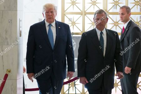 Donald Trump, John Roberts. President Donald Trump, left, walks with Supreme Court Chief Justice John Roberts as he arrives to view the casket of Justice John Paul Stevens at the Supreme Court, in Washington