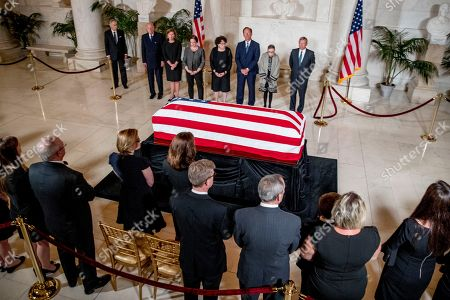 From center left, retired Associate Justice Anthony Kennedy, Ashley Kavanaugh, the wife of Associate Justice Brett Kavanaugh, Associate Justice Elena Kagan, Associate Justice Judge Sonia Sotomayor, Associate Justice Samuel Alito, Associate Justice Ruth Bader Ginsburg, and Chief Justice John Roberts participates in a ceremony along with family, below, for the late Supreme Court Justice John Paul Stevens as he lies in repose in the Great Hall of the Supreme Court in Washington