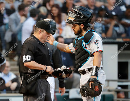 Miami Marlins catcher Jorge Alfaro, right, pats home plate umpire Marty Foster, left, on the shoulder after Foster recovered from being struck by a foul tip off the bat of Chicago White Sox's Adam Engel during the second inning of a baseball game, in Chicago
