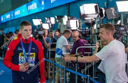 Third placed Duncan Scott (L) of Great Britain is being celebrated by other swimmers, coaches and most of the crowd on his way out after refusing to pose with winner Yang Sun of China (not pictured) during the medal ceremony for the men's 200m Freestyle Final during the Swimming events at the Gwangju 2019 FINA World Championships, Gwangju, South Korea, 23 July 2019.