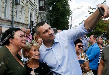 Former heavyweight boxing champion, now Kiev Mayor Vitali Klitschko takes a selfie photo with people in center Kiev, Ukraine