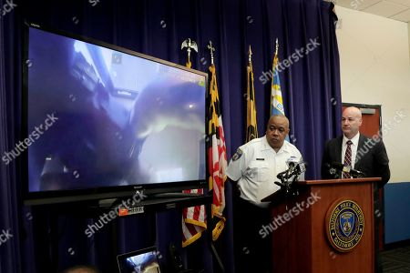 Baltimore Police Commissioner Michael Harrison, center, and Capt. Donald Diehl look on as the department makes public portions of footage from the body camera worn by Sgt. Billy Shiflett, who was shot while responding to an active shooter call at Baltimore addiction clinic at a news conference, in Baltimore. Shiflett was wearing a bulletproof vest but a bullet shot by a man demanding methadone struck his lower abdomen on July 15. The officer was released from the hospital over the weekend