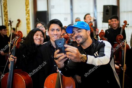 Puerto Rican singer Luis Fonsi (R) poses with members of the 'Sinfonia por el Peru' (Symphony for Peru) orchestra during an encounter with children and youngsters of the social and education project, in Lima, Peru, 23 July 2019, as part of the activities prior to the opening of the Pan American Games Lima 2019. Lima 2019 Pan American Games are held between 26 July and 11 August.