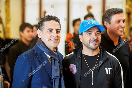 Puerto Rican singer Luis Fonsi (R) and Peruvian Juan Diego Florez, founder of the 'Sinfonia por el Peru' (Symphony for Peru) orchestra, pose during an encounter with children and youngsters of the social and education project, in Lima, Peru, 23 July 2019, as part of the activities prior to the opening of the Pan American Games Lima 2019. Lima 2019 Pan American Games are held between 26 July and 11 August.