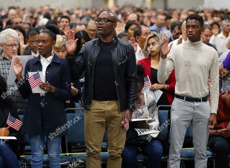 """Mixed martial arts great Anderson """"Spider"""" Silva of Brazil, center, his daughter Kaory, 23, left, and son Kalyl, 20, are is sworn in as a U.S. citizen along with thousands of others in a mass naturalization ceremony Tuesday at the Los Angeles Convention Center"""