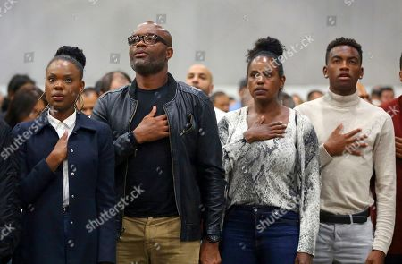 """Mixed martial arts great Anderson """"Spider"""" Silva of Brazil, his daughter Kaory, 23, left, his wife Dayane and son Kalyl, 20, right, recite the Pledge of Allegiance after all but Dayane were sworn in as U.S. citizens in a mass naturalization ceremony Tuesday at the Los Angeles Convention Center"""