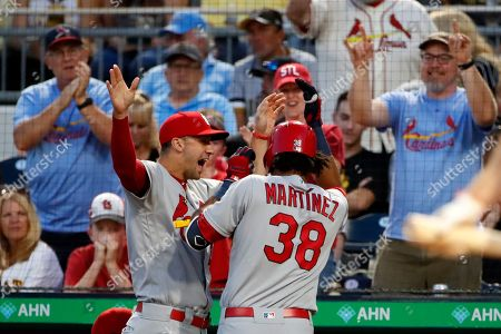 St. Louis Cardinals' Jose Martinez (38) is greeted at the dugout steps by Jack Flaherty after hitting a solo home run off Pittsburgh Pirates starting pitcher Chris Archer during the fifth inning of a baseball game in Pittsburgh
