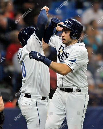 Tampa Bay Rays' Mike Zunino, left, greets Travis d'Arnaud at the plate after scoring on d'Arnaud's two-run home run off Boston Red Sox starter Chris Sale during the third inning of a baseball game, in St. Petersburg, Fla
