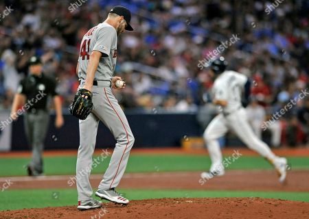 Boston Red Sox starter Chris Sale walks up the mound as Tampa Bay Rays' Travis d'Arnaud, right, circles the bases after hitting a two-run home run during the third inning of a baseball game, in St. Petersburg, Fla