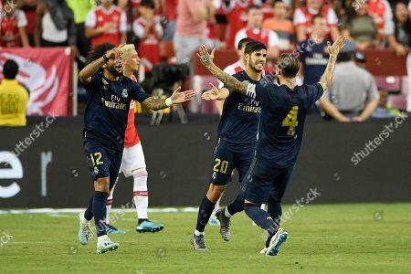 Real Madrid midfielder Marco Asensio (20) celebrates his goal with Marcelo (12) and Sergio Ramos (4) during the second half of an International Champions Cup soccer match against Arsenal, in Landover, Md. The game ended 2-2 and Real Madrid won 3-2 after penalty kicks