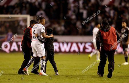 A boy who invaded the pitch hugs Antonio Valencia of Ecuador's Liga Deportiva Universitaria during a Copa Libertadores match in Quito, Ecuador