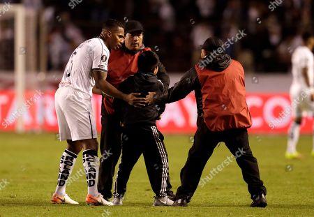 A boy who invaded the pitch is ushered out by Antonio Valencia of Ecuador's Liga Deportiva Universitaria during a Copa Libertadores match in Quito, Ecuador
