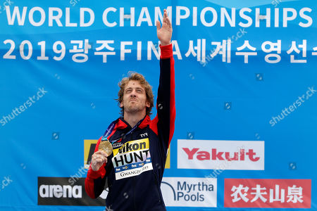 Gold medalist Gary Hunt of Britain gestures as he stands on the podium after the men's high diving competition at the World Swimming Championships in Gwangju, South Korea