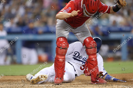 Los Angeles Dodgers catcher Russell Martin (55) collides with the leg of Los Angeles Angels catcher Dustin Garneau (13) on a force out at home plate during the game between the Los Angeles Angels of Anaheim and the Los Angeles Dodgers at Dodger Stadium in Los Angeles, CA. (Photo by Peter Joneleit)