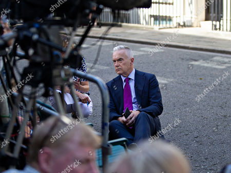 BBC News presenter Huw Edwards sits on the ground in Downing Street