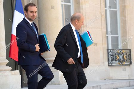 French Junior Minister for territorial communities Sebastien Lecornu (L) and French Foreign Affairs Minister Jean-Yves Le Drian leaving the last weekly cabinet meeting before the government goes on holidays, at the Elysee Presidential palace.
