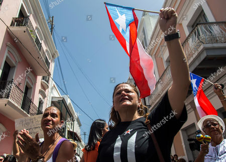 Ex-New York City councilwoman Melissa Mark-Viverito, center, joins protesters outside La Fortaleza, in San Juan, Puerto Rico, . Hundreds of thousands of Puerto Rico have been outraged by leaked, obscenity-laced online chats between Gov. Ricardo Rossello and his advisers, and have protested for nearly two weeks demanding his resignation