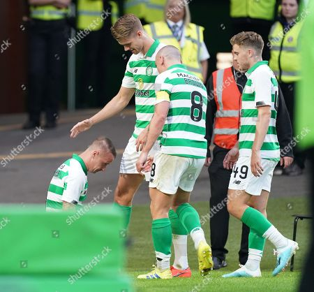 Leigh Griffiths of Celtic is congratulated by team mates as he falls to his knees amid emotional celebrations after he scored to give Celtic a 3-0 lead. Griffiths has just returned to the team following a period out with mental health issues.