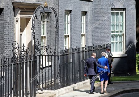 Theresa May, with husband Philip May putting his arm around her, leaves Number 10 Downing Street