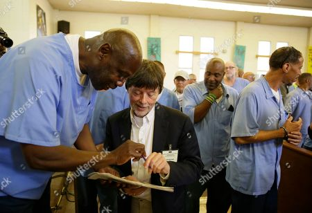 Filmmaker Ken Burns signs an autograph for an inmate at San Quentin State Prison in San Quentin, Calif. Burns visited the prison to show parts of his new documentary, Country Music, that premieres Sept. 15 on PBS. The clips shown at the prison included sections from the film about Johnny Cash's iconic performances at San Quentin, one of which inspired then-inmate Merle Haggard to pursue his own music career