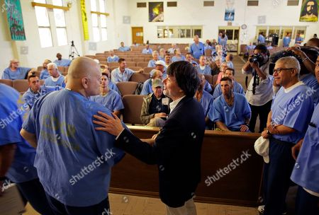 Filmmaker Ken Burns is greeted by inmates at San Quentin State Prison before showing parts of his new documentary, Country Music, in San Quentin, Calif. Burns visited the prison to show parts of his eight-part, 16-hour documentary that premieres Sept. 15 on PBS. The clips shown at the prison included sections from the film about Johnny Cash's iconic performances at San Quentin, one of which inspired then-inmate Merle Haggard to pursue his own music career