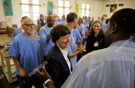 """Filmmaker Ken Burns is greeted by inmates at San Quentin State Prison after showing parts of his new documentary, """"Country Music,"""", in San Quentin, Calif. Burns visited the prison to show parts of his eight-part, 16-hour documentary that premieres Sept. 15 on PBS. The clips shown at the prison included sections from the film about Johnny Cash's iconic performances at San Quentin, one of which inspired then-inmate Merle Haggard to pursue his own music career"""