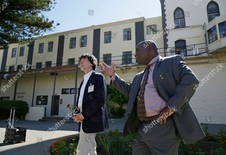 Filmmaker Ken Burns, left, is led into San Quentin State Prison by public information officer Lt. Sam Robinson, in San Quentin, Calif. Burns visited the prison to show parts of his new eight-part, 16 hour documentary, Country Music, that premieres Sept. 15 on PBS. The clips shown at the prison included sections from the film about Johnny Cash's iconic performances at San Quentin, one of which inspired then-inmate Merle Haggard to pursue his own music career